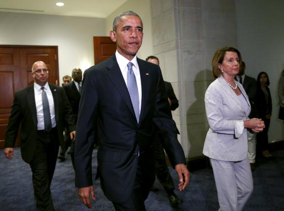 U.S. President Barack Obama, with House Democratic leader Nancy Pelosi at his side, walks from a meeting room to make a last-ditch appeal to House Democrats to support a package of trade bills vital to his Asian policy agenda in the U.S. Capitol in Washington June 12, 2015.  REUTERS/Kevin Lamarque